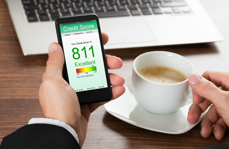 closeup of credit score on a man's phone showing 811 with a cup of coffee and laptop sitting nearby