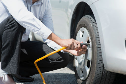 driver checking their tire pressure