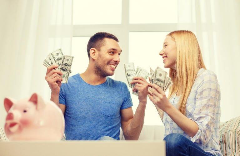 Happy couple with cash in their hands
