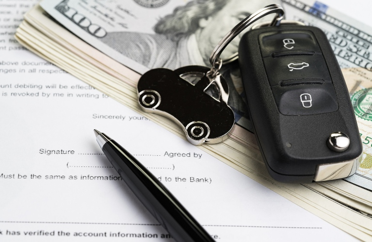 Key and money on top of paperwork for a vehicle