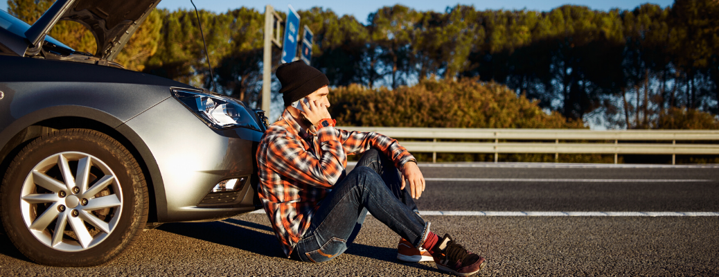 Young man sitting on the road next to damaged car with open hood_b