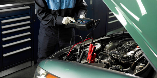 Mechanic checking car's battery with tester