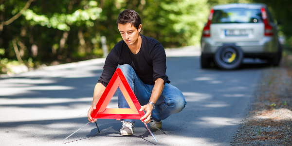 Young man placing triangle reflector a few feet behind broken vehicle