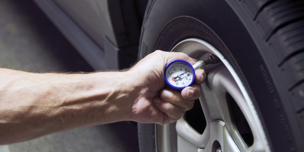 Male hand checking tire pressure with gauge
