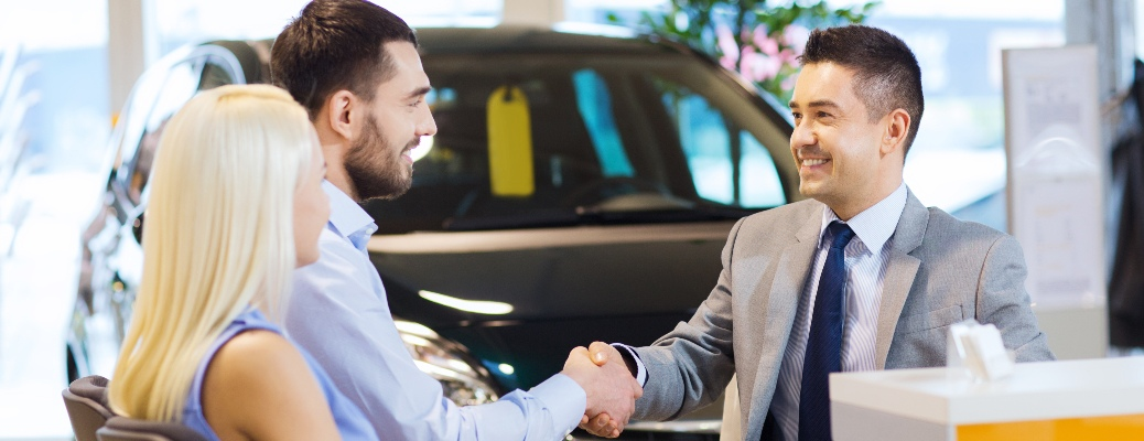 Car salesman and man shaking hands