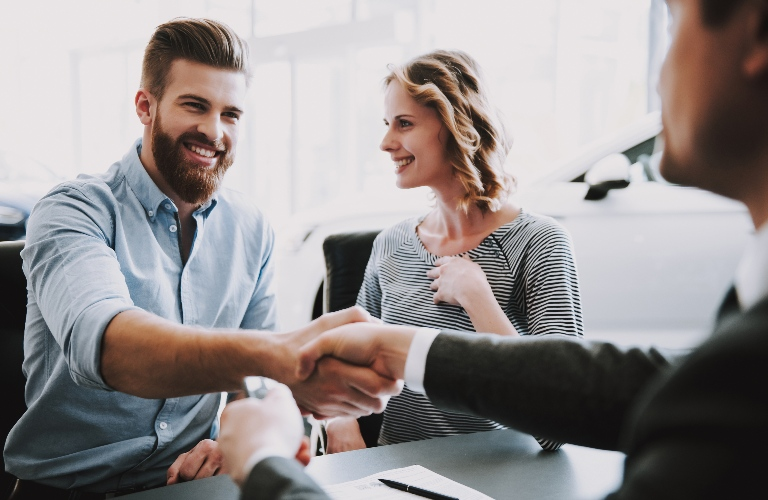 Man and sales man shaking hands with wife looking happy