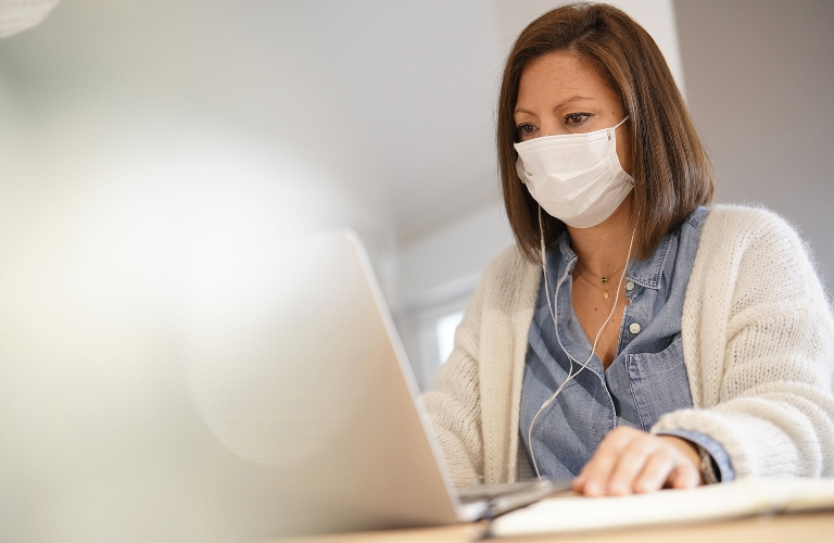 Woman working on a computer with a mask on