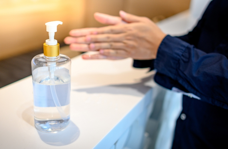 Person washing hands with hand sanitizer