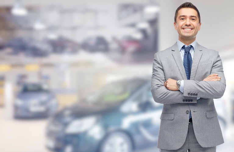 Car salesman standing in front of blurred out cars