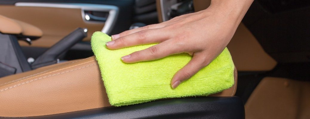 A stock photo of a person detailing the inside of their vehicle.