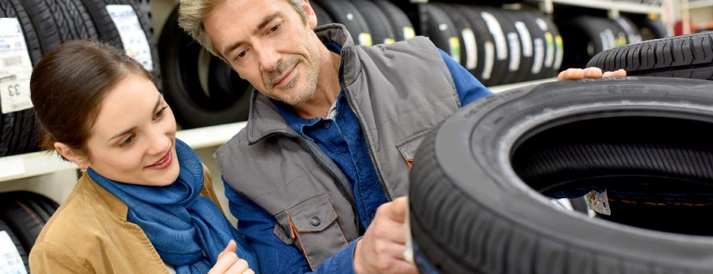 A stock photo of people looking at tires.