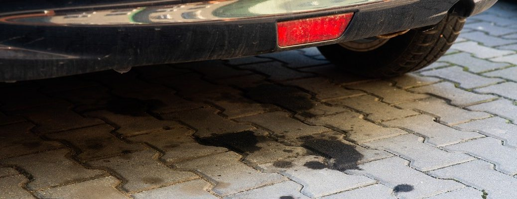 A stock photo of oil spots under a car on a driveway.