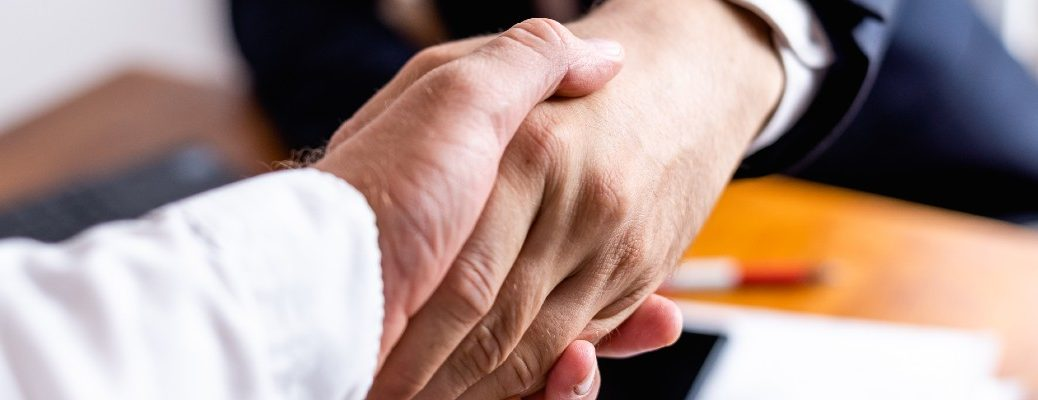 A stock photo of people shaking hands after completing a deal.