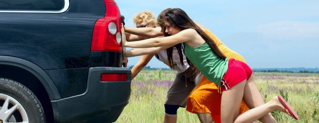 A stock photo of people pushing a broken down vehicle.