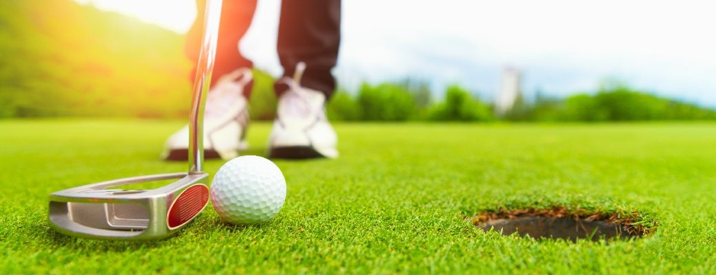 A stock photo of a person lining up a putt.