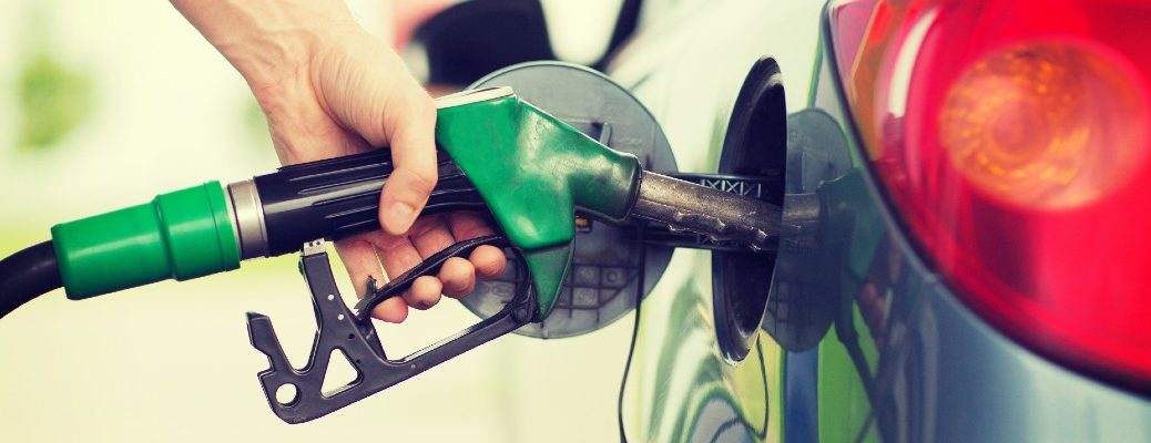 A stock photo of a person filling their car up with fuel.