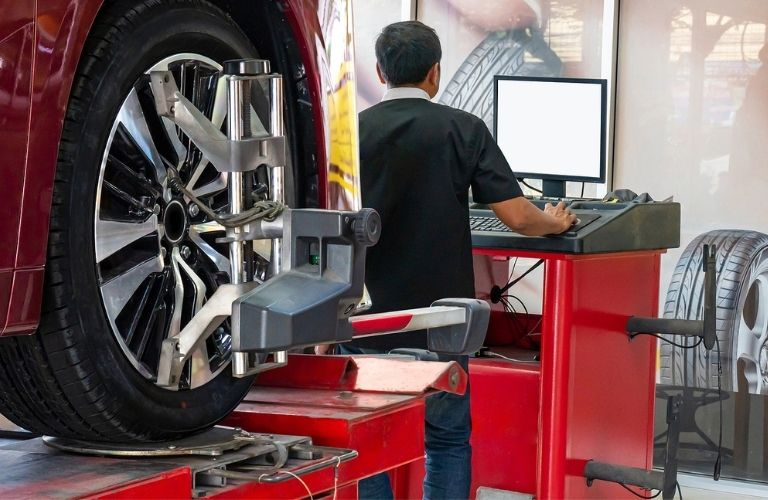 A Man correcting the tires using a machine