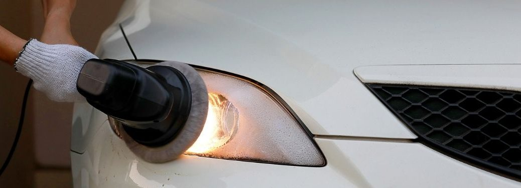 man cleaning a cloudy headlight