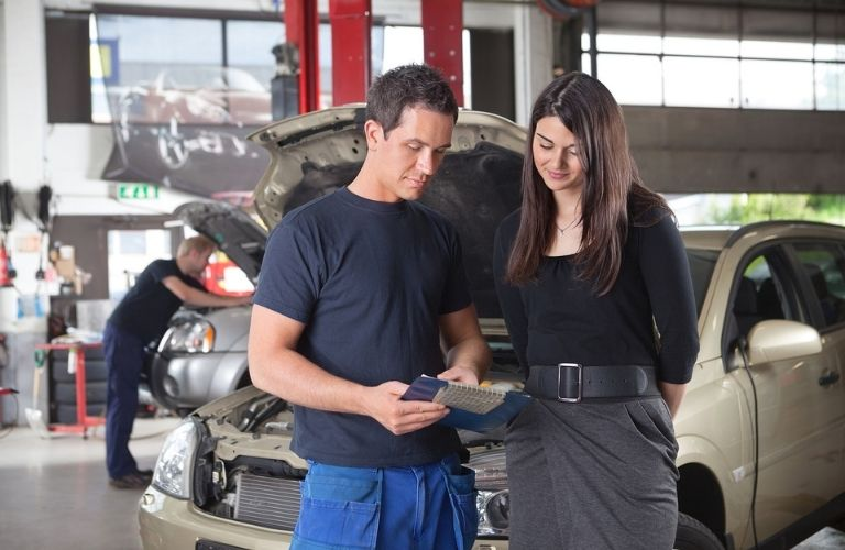 mechanic showing the cost of service to a woman