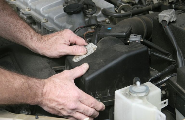 hands of a mechanic on the filter cover of a car