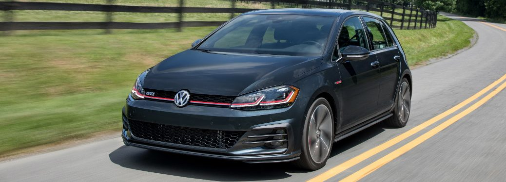 Black 2018 VW Golf GTI Driving by a Grassy Field