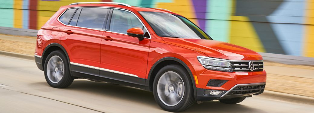 Orange 2018 VW Tiguan Driving by a Colorful Wall