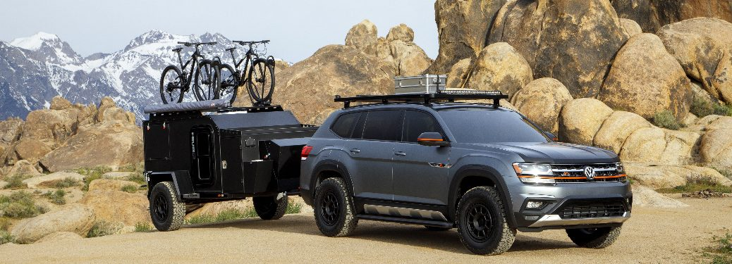 Grey Volkswagen Atlas Basecamp with a camping trailer parked in front of large rock formations