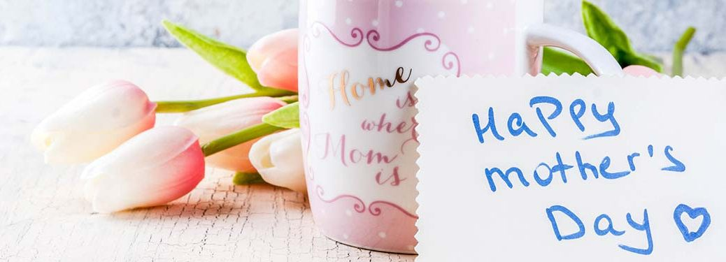 Happy Mother's Day note, a pink mug, and flowers