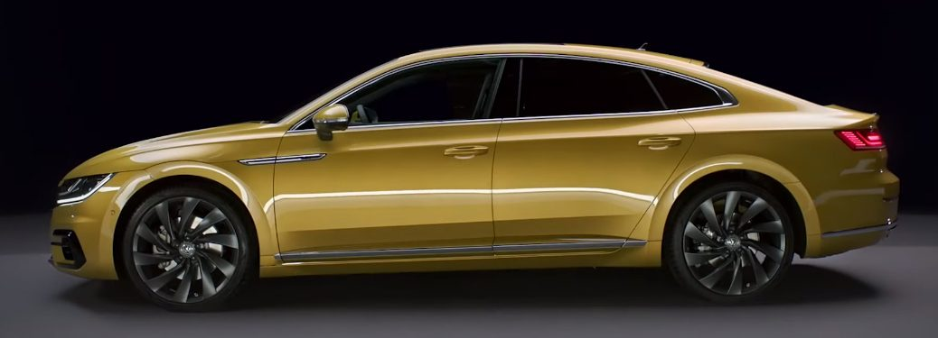 Side view of yellow 2019 Volkswagen Arteon with a black background
