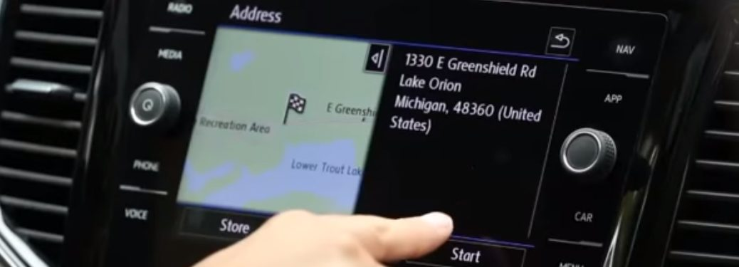 A driver entering a destination into the Volkswagen Navigation System