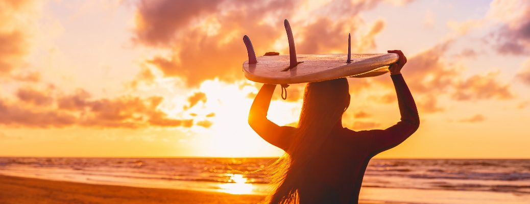 A woman holding a surfboard on her head with the sunset in the background