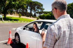 teen driver in car near cones, instructor taking notes