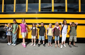 kids lined up in front of school bus