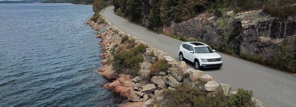 aerial view of white volkswagen atlas driving by water