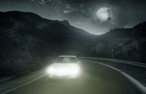 white car with headlights on driving at night