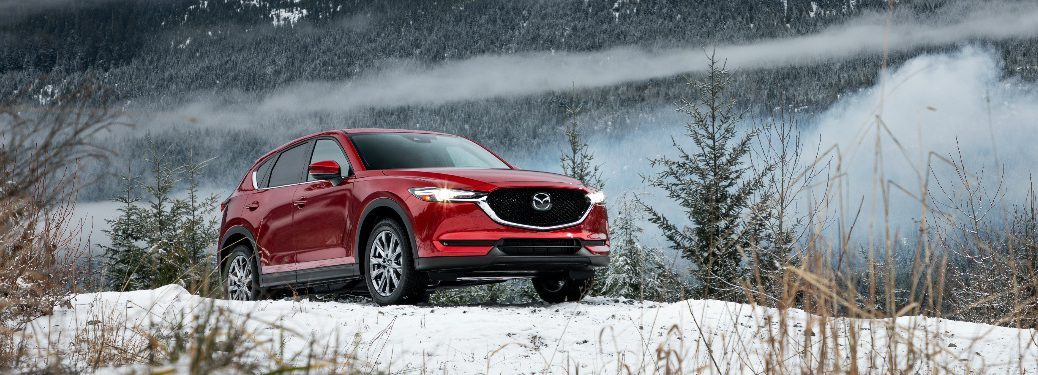 Red 2019 Mazda CX-5 driving on snowy terrain with mountains in the background