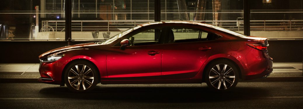 Red 2019 Mazda6 driving by a building with large glass windows