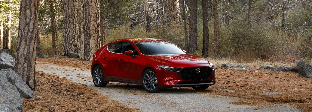 Red 2019 Mazda3 Hatchback parked on a road in a forest