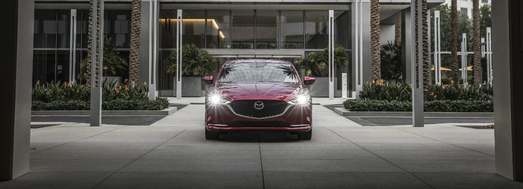 front view of red mazda6 with headlights on