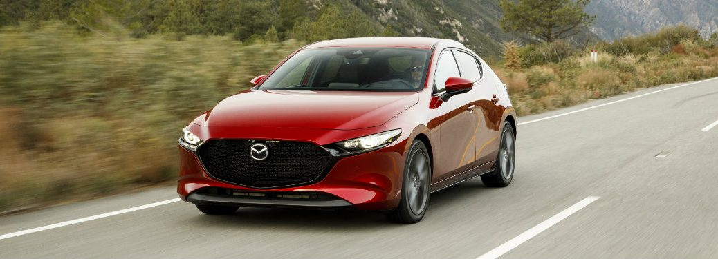 front view of red mazda3 driving