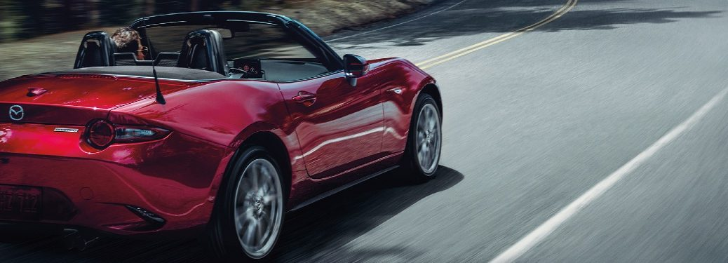 2020 Miata driving on wooded road, rear exterior view