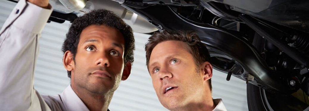 two people inspecting car undercarriage