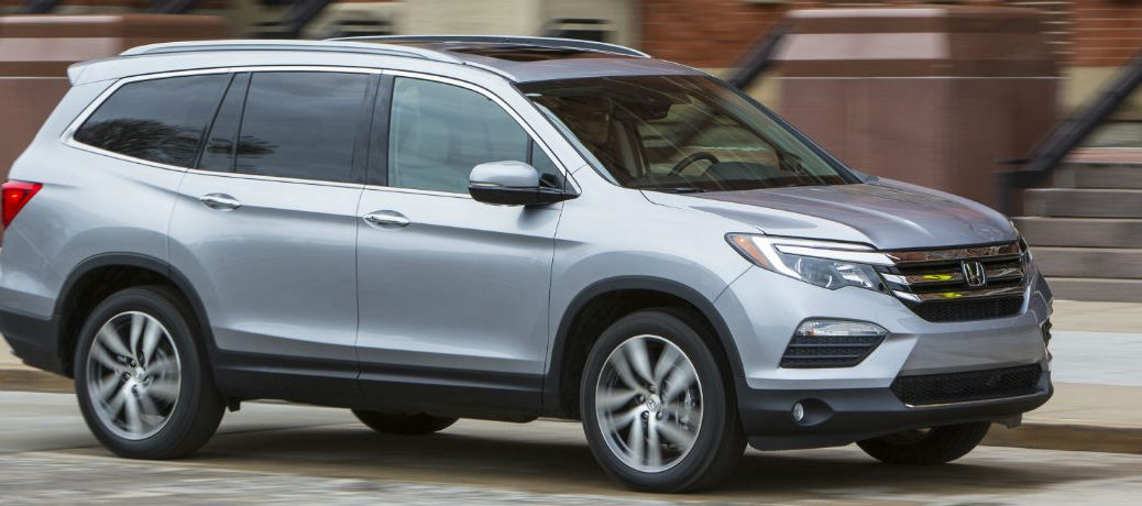 Exterior view of a silver 2018 Honda Pilot parked on a street