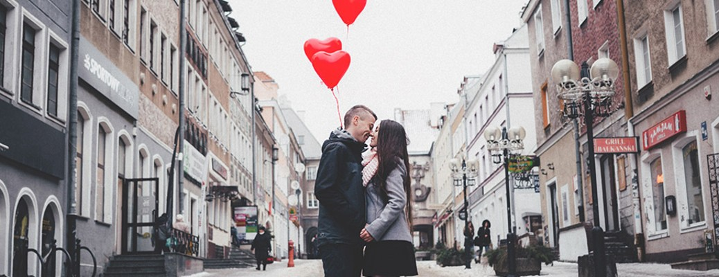 a couple with heart balloons in a city