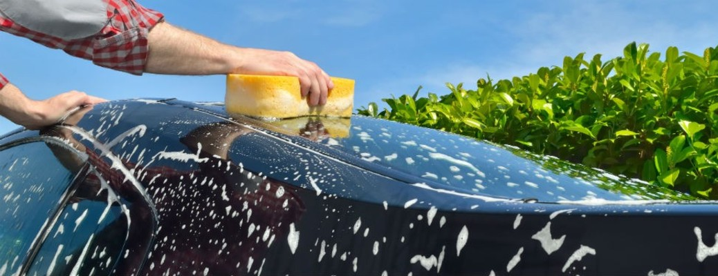 a hand with a sponge on a car's exterior