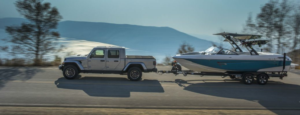 A photo of the 2020 Jeep Gladiator pulling a boat near a mountain lake.