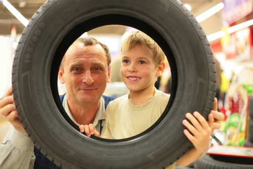 A man and a child hold a tire and stare through the hold in its center.