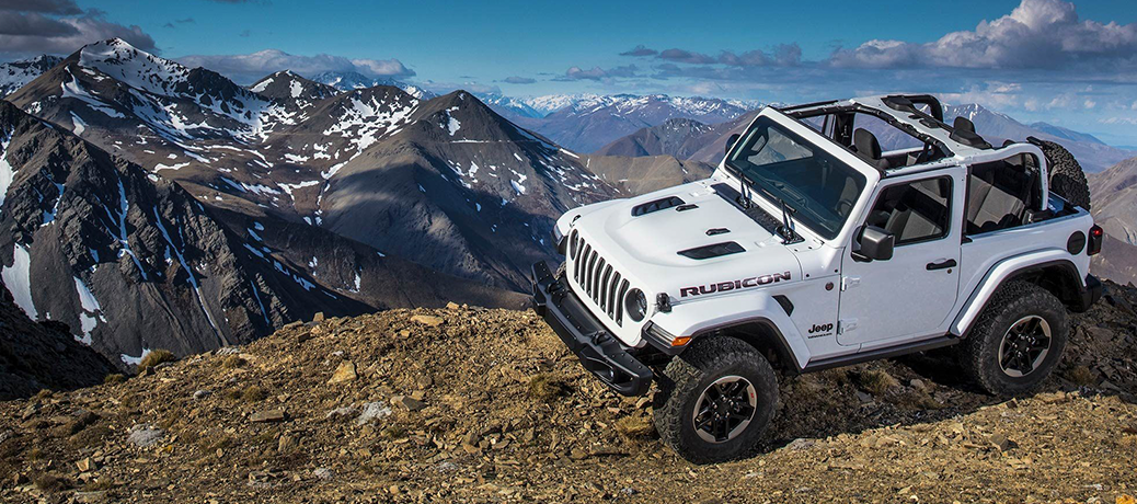 White 2019 Jeep Wrangler rolls along the top of a mountain.