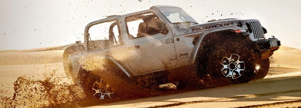2020 Jeep Wrangler white side view going up a sand dune