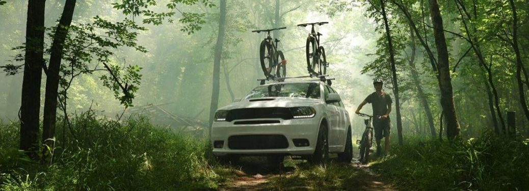 White 2020 Dodge Durango in the woods with bikes on top from front